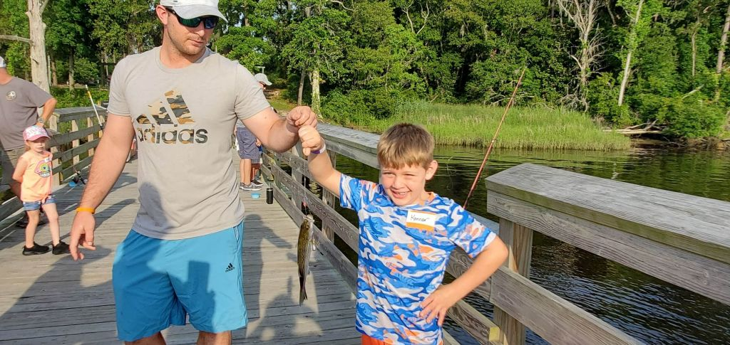 Photo of boy and man on fishing dock